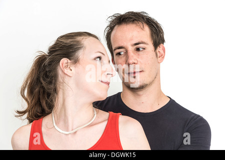 Couple looking each other in the eye, woman standing in front of a man and looking lovingly back towards him - Stock Photo