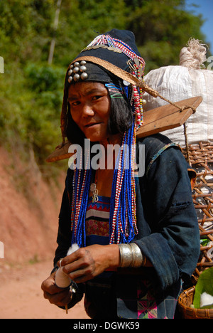 Poverty, portrait, woman of the Akha Djepia ethnic group, traditional colorful clothes, cap for a hat, spinning - Stock Photo