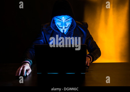 Young man wearing an anonymous mask and a hood sitting in front of a laptop - Stock Photo