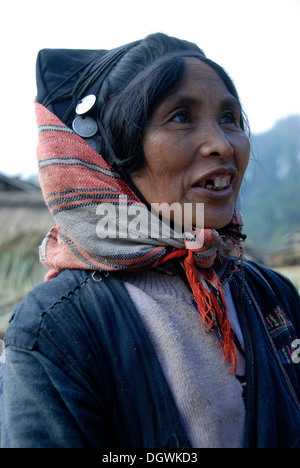 Portrait, smiling woman of the Akha Phixor ethnic group, traditional clothing dyed with indigo, headdress, cap with - Stock Photo