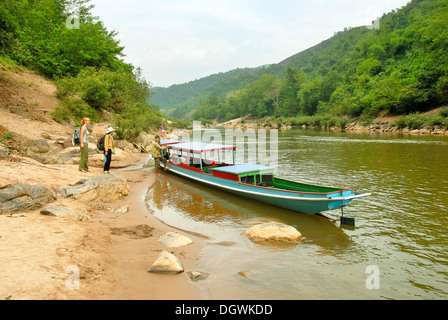 Tourists on the shore, river valley, wooden boat on the Nam Ou river in Muang Khoua, Phongsali province, Laos, Southeast Asia