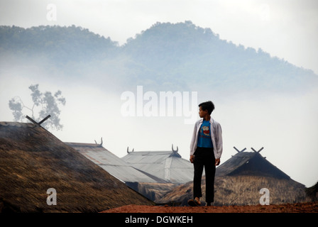 Boy in front of the houses of the Phixor Akha ethnic group, village Ban Mososane, thatched roofs, fog and mountains - Stock Photo