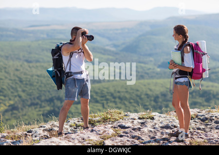 Two tourists. Man photographs woman, she is holding a map. - Stock Photo