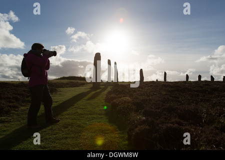Islands of Orkney, Scotland. Picturesque silhouetted view of a lady photographer working at Orkney's historic Ring - Stock Photo
