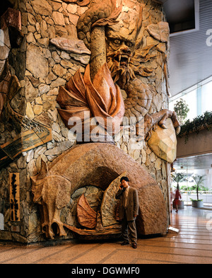 Lobby of the Lippo Centre, artwork made of stone with a man using a mobile phone standing in front, detail, glass - Stock Photo