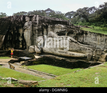 Reclining Buddha, entrance to Nirvana, a tourist standing in front of the Gal Vihara rock temple, UNESCO World Heritage - Stock Photo