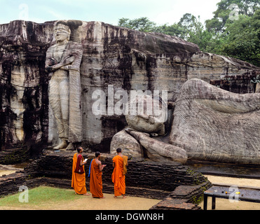 Reclining Buddha, entrance to Nirvana, three monks standing in front of the Gal Vihara rock temple, UNESCO World - Stock Photo