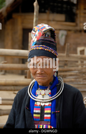 Portrait of old woman of the Akha Loma ethnic group, traditional black costume, colourfully embroidered, cap, silver - Stock Photo