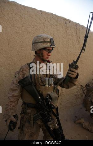 A U.S. Marine with India Company, 3rd Battalion, 7th Marine Regiment (3/7), checks a radio during a patrol near - Stock Photo