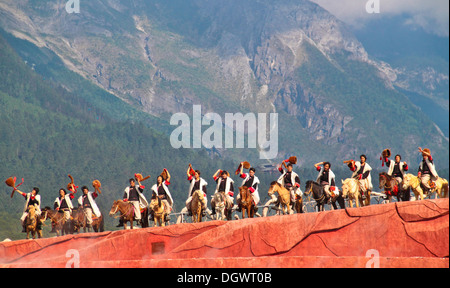 Dancers on horse back waving hands during 'Impression of Lijiang' cultural show at Lijiang, Yunnan China. - Stock Photo