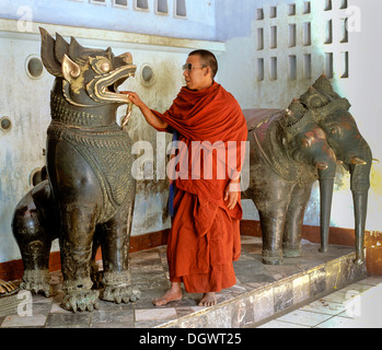 Monk placing his hand into the mouth of a lion statue, in front of a statue of Airavata, the three-headed elephant - Stock Photo