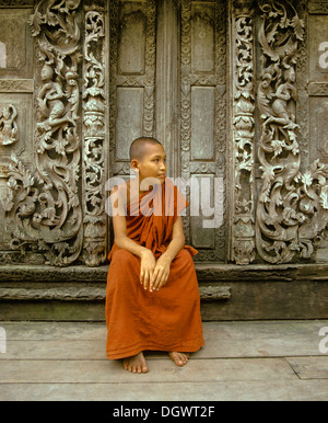 Monk sitting in front of a wooden door with teak carvings, Shwe In Bin Kyaung Monastery, Mandalay, Mandalay Division, - Stock Photo