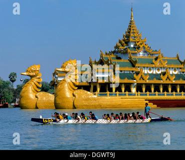 Dragon boat on Lake Kandawgyi in front of the Karaweik ship restaurant, Rangun, Yangon Region, Myanmar, Burma - Stock Photo