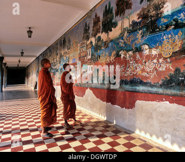 Monks standing in front of a wall painting from the Ramayana epic in the Silver Pagoda or Preah Vihear Preah Keo - Stock Photo