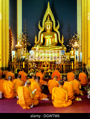Monks at prayer in front of the Phra Phutthachinnarat, Buddha statue in the marble temple of Wat Benchamabophit, - Stock Photo