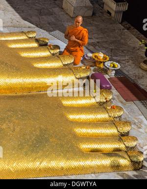 Monk praying at the feet of the golden Buddha statue of Wat Intharawihan, Wat Indra, Bangkok, Central Thailand, - Stock Photo