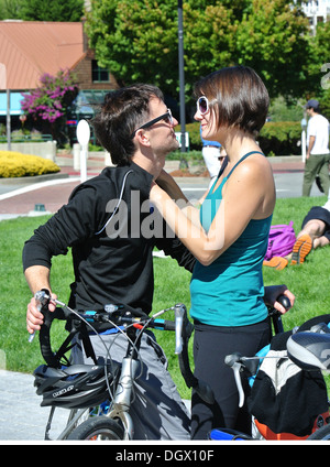 couple on bikes hugging and looking at each other at Tiburon ferry - Stock Photo