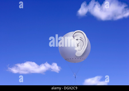 Tethered balloon with a three-dimensional human ear against a blue sky with white clouds, symbolic image for bugging - Stock Photo
