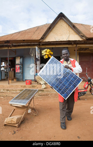 Mr. Tinkasimire, owner of an electrical shop, offering products like Premier Modul solar panels, Masindi, Uganda, - Stock Photo