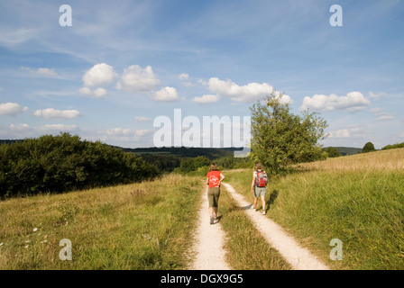 Two hikers on a dirt road near Riedenburg in Altmuehltal Nature Park, Bavaria - Stock Photo