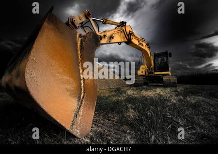 Backhoe bucket excavators with a dramatic sky - Stock Photo