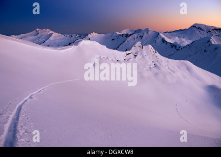 Mountain landscape with ski tracks in the pristine snow at dawn, Baad, Kleinwalsertal, Vorarlberg, Austria - Stock Photo