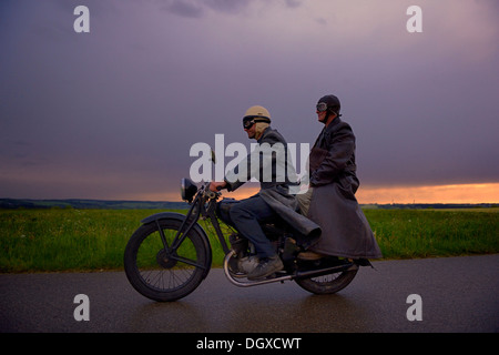 Two vintage motorcyclists in front of a dramatic cloudy sky, Mindelheim, Unterallgäu District, Bavaria, Germany - Stock Photo