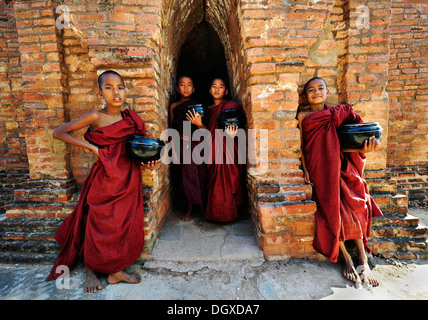 Young Buddhist novices holding alms bowls in front of the old monastery walls at the Shwezigon Pagoda in Bagan, - Stock Photo