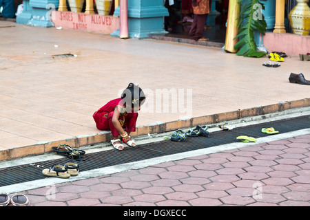 Little girl putting on her shoes outside the temple in Batu Caves, Selangor, Malaysia - Stock Photo