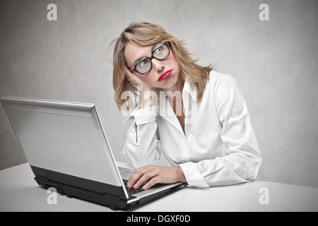 Bored blonde woman with glasses using a laptop - Stock Photo