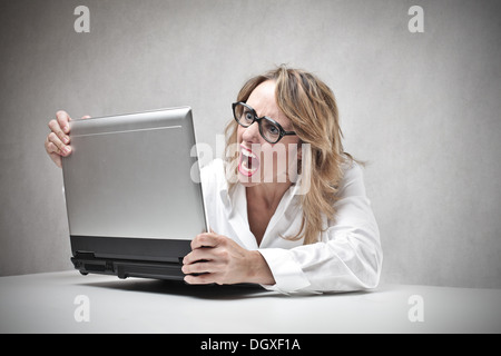Blonde woman with glasses screaming against a laptop - Stock Photo
