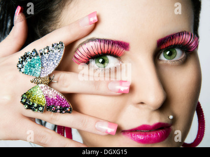 Young woman wearing artificial eyelashes and a butterfly as a ring, Austria - Stock Photo