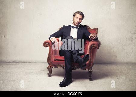 Gentleman sitting on a vintage armchair - Stock Photo