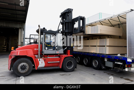 Fork lifter loading the finished particle boards onto a truck, Pfleiderer AG factory at the headquarters in Neumarkt - Stock Photo