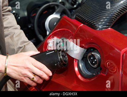 A woman 'refuelling' a Tesla Roadster battery electric vehicle at a charging station, Starnberg, Bavaria - Stock Photo