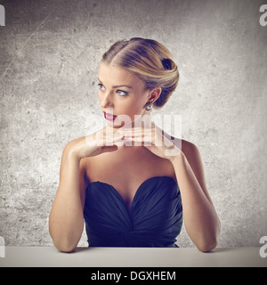 Beautiful blonde girl leaning against a table - Stock Photo