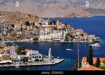 Overlooking the picturesque houses and the clock tower of the small island of Symi near Rhodes, Greece, Europe - Stock Photo