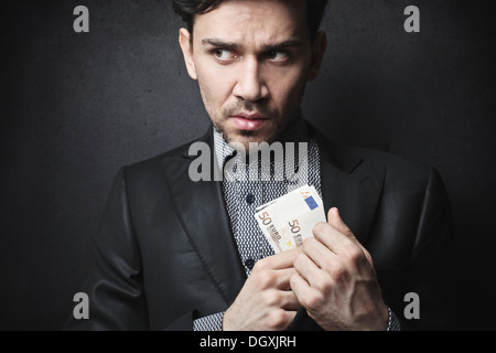 Elegant man hiding fifty euro banknotes in his suit jacket - Stock Photo