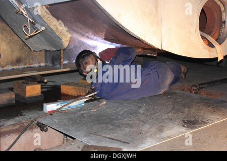 A welder welding new support plates - Stock Photo