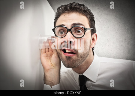 Office worker with glasses trying to hear through a wall - Stock Photo
