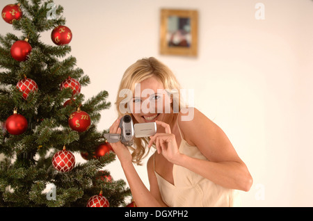 Blonde woman, 20-30, wearing an evening dress while filming with a camcorder in front of a Christmas tree - Stock Photo