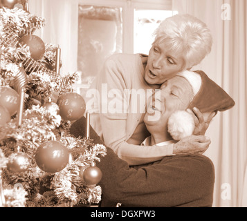 Mature couple, man with a Santa hat, by a Christmas tree - Stock Photo
