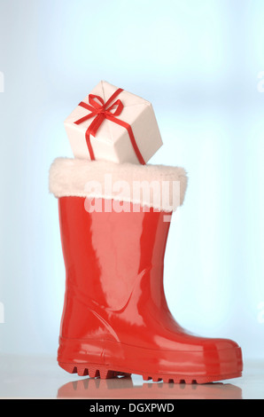 Red rubber Santa Claus boot with a gift - Stock Photo