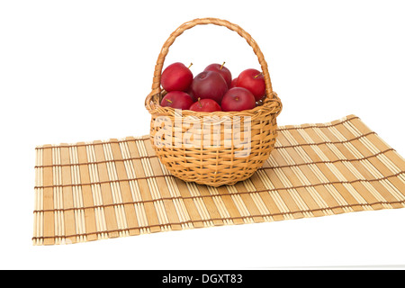 Plums in a wicker basket on a napkin isolated on white background - Stock Photo
