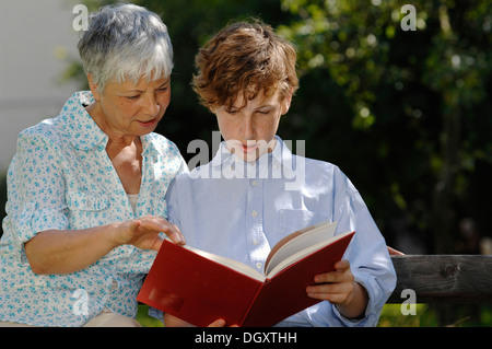 Grandmother and grandson are looking at a red book together on park bench