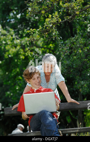 Grandson and grandmother looking together at a laptop computer on a park bench