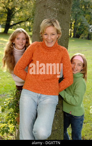 Mother and two daughters standing around a tree in a park - Stock Photo