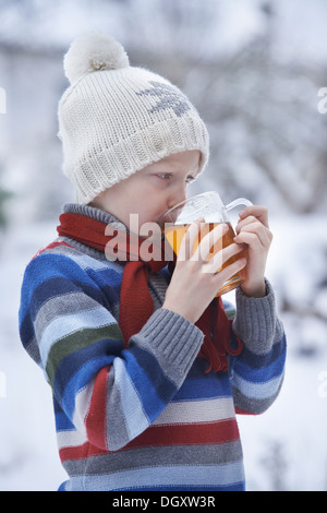 Boy in winter clothes drinking tea - Stock Photo