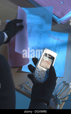 Burglar using a camera phone to take a photograph of secret plans, symbolic image for industrial espionage - Stock Photo