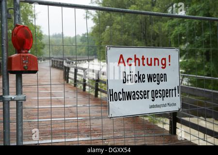 Barrier with a warning sign, 'Achtung! Brücke wegen Hochwasser gesperrt!', German for 'Attention! Bridge closed - Stock Photo